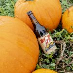 Red Racer Snickerdoodle Pumpkin Ale Bottle Leaning on Pumpkins